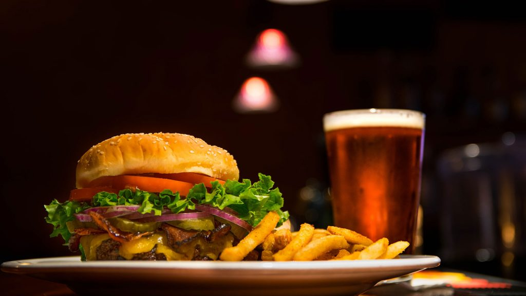 Hamburger with fries and a glass of beer.